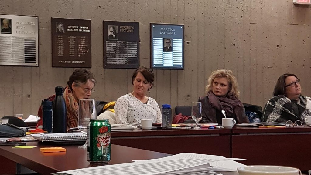 Three women sitting at a board table in a room with plaques on the wall. One is speaking, the others looking at her.